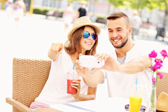 Happy couple taking pictures in a cafe Royalty Free Stock Images