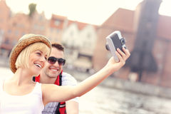 Happy couple taking pictures in a canoe Stock Photo