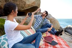 Happy couple taking pictures during a relaxed picnic on the rock Royalty Free Stock Image