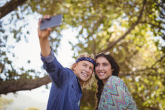 Happy couple taking selfie against trees Stock Image