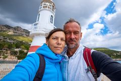 Happy couple taking selfie on the background of the lighthouse royalty free stock photo