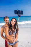 Happy couple taking a selfie at the beach Stock Photography