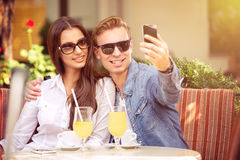 Happy couple taking selfie in a cafe Stock Photos