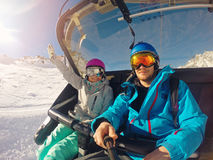 Happy couple taking selfie in chairlift at ski resort stock photography