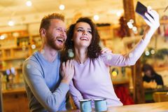 Happy couple taking selfie in coffee shop Stock Photography