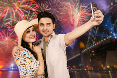 Happy couple taking selfie with fireworks background Stock Images