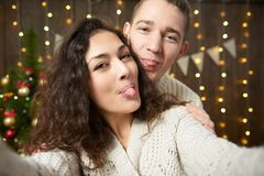 Happy couple taking selfie and having fun in christmas decoration. Dark wooden interior with lights. Romantic evening and love con. Cept. New year holiday Stock Photos