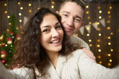 Happy couple taking selfie and having fun in christmas decoration. Dark wooden interior with lights. Romantic evening and love con. Cept. New year holiday Royalty Free Stock Photography