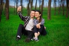 Happy couple taking selfie holding smartphone stock image