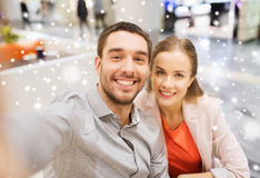Happy couple taking selfie in mall or office. Technology, photographing, and people concept - happy couple taking selfie with smartphone or camera in mall with Stock Photography
