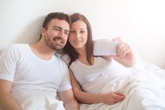 Happy couple taking a selfie with mobile phone Stock Image
