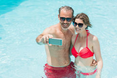 Happy couple taking selfie from mobile phone in pool. On a sunny day royalty free stock photos