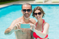 Happy couple taking selfie from mobile phone in pool. On a sunny day stock photography