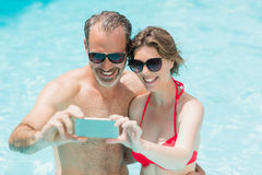 Happy couple taking selfie from mobile phone in pool. On a sunny day stock photos