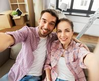 Happy couple taking selfie at new home stock photo