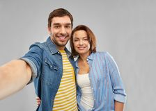 Happy couple taking selfie over grey background. People concept - happy couple hugging and taking selfie over grey background stock image