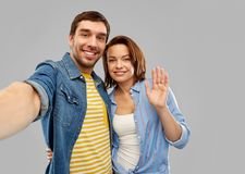 Happy couple taking selfie over grey background. People concept - happy couple hugging and taking selfie over grey background stock images