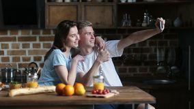 Happy couple taking selfie with phone in kitchen stock video footage