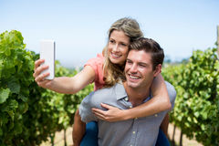 Happy couple taking selfie while piggybacking at vineyard against sky Royalty Free Stock Image