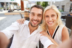 Happy couple taking selfie at restaurant terrace. Love, date, technology, people and relations concept - smiling happy couple taking selfie at restaurant terrace Stock Image