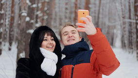 Happy couple taking selfie. Happy  romantic couple have fun in fresh snow and taking selfie. Romantic winter scene in forest with young people stock footage