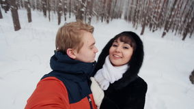 Happy couple taking selfie. Happy  romantic couple have fun in fresh snow and taking selfie. Romantic winter scene in forest with young people stock video