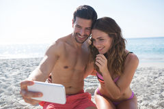 Happy couple taking selfie while sitting at beach Royalty Free Stock Photos