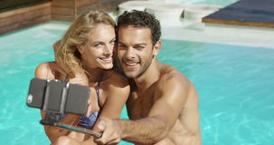 Happy couple taking selfie. Sitting by the pool stock video