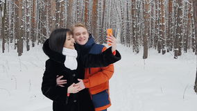 Happy couple taking selfie in slowmotion. Happy  romantic couple have fun in fresh snow and taking selfie. Romantic winter scene in forest with young people stock video footage
