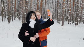 Happy couple taking selfie in slowmotion. Happy  romantic couple have fun in fresh snow and taking selfie. Romantic winter scene in forest with young people stock video