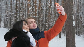 Happy couple taking selfie in slowmotion. Happy  romantic couple have fun in fresh snow and taking selfie. Romantic winter scene in forest with young people stock footage