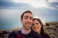 Happy couple taking selfie with smartphone or camera over sunset Stock Images