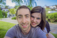Happy couple taking selfie with smartphone or camera in the park Royalty Free Stock Photo