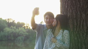 Happy couple taking selfie with the smartphone in the park stock footage