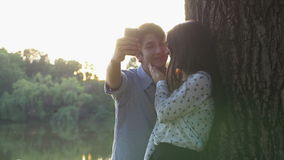 Happy couple taking selfie with the smartphone in the park stock video