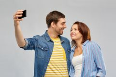 Happy couple taking selfie by smartphone. Technology and people concept - happy couple hugging and taking selfie by smartphone over grey background stock photography