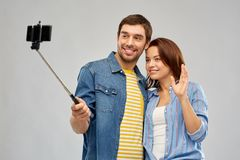 Happy couple taking selfie by smartphone. Technology and people concept - happy couple hugging and taking picture by smartphone and selfie stick over grey royalty free stock photography