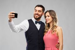 Happy couple taking selfie by smartphone royalty free stock images