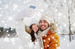 Happy couple taking selfie by smartphone in winter Royalty Free Stock Photos