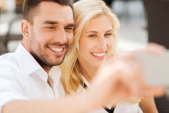 Happy couple taking selfie with smatphone outdoors Stock Image