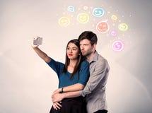 Happy couple taking selfie with smiley Stock Photos