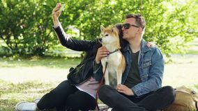 Happy couple is taking selfie with their dog using smartphone sitting on grass in the park, people are posing, talking. And petting shiba inu puppy. Photograph stock video