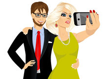 Happy couple taking a selfie using her smartphone. Portrait of happy blonde woman and young hipster man in business suit taking a selfie using her smartphone Royalty Free Stock Image