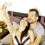 Happy couple taking selfie in vacation in hotel bedroom Royalty Free Stock Images