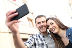 Happy couple taking selfies with smartphone in the street stock image