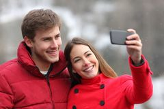 Happy couple taking selfies in winter holiday. Happy couple taking selfies with a smart phone in winter holiday royalty free stock photos