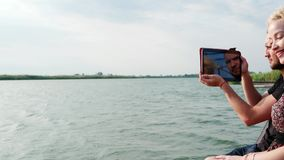 Happy couple taking video of wonderful view by tablet, boy and girl using tablet at lakeside stock video footage