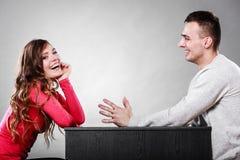 Happy couple talking on date. Conversation. Happy couple talking and laughing on date. Smiling girl and guy having conversation. Amusing men making women laugh royalty free stock photo