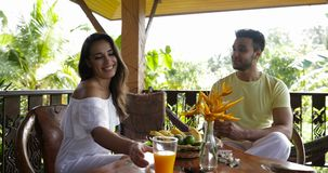 Happy Couple Talking Drink Orange Juice Sitting On Terrace In Tropical Forest, Young Man And Woman Communication During stock footage