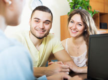 Happy couple talking with employee royalty free stock photography